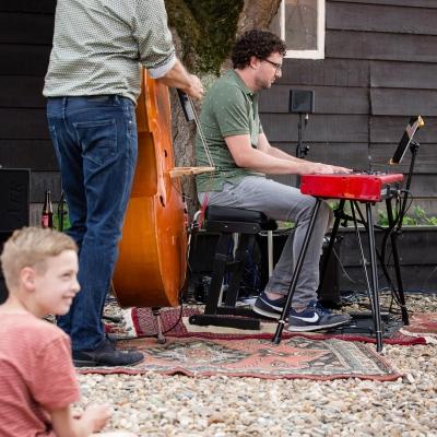 HEIJBLOM FOTOGRAFIE-Piano-spelen-en-bassen-op-een-perzisch-kleed-in-de-tuin-bij-Door Visser-Music-en-jongen-kijkt-toe