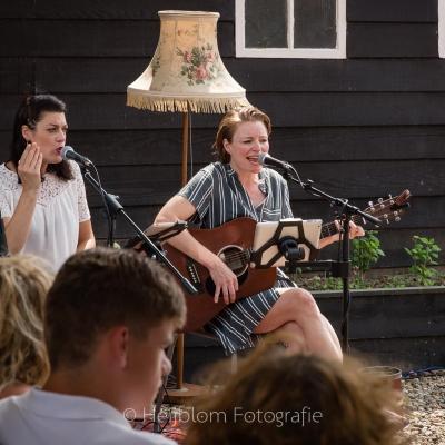 HEIJBLOM FOTOGRAFIE-Door Visser-zangeres-met-eitje-en-zangeres-met-gitaar-tijdens-optreden-tuinconcert-Numansdorp-Door-Visser