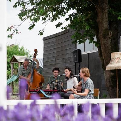 HEIJBLOM FOTOGRAFIE-Lavendel-met-hek-en-de-band-van-Door Visser-Music-in-de-tuin-tijdens-concert