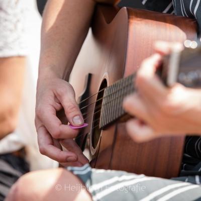 HEIJBLOM FOTOGRAFIE-Vrouw-speelt-gitaar-met-roze-plectrum-tijdens-tuinconcert-Door Visser