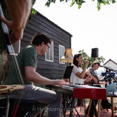 HEIJBLOM FOTOGRAFIE-Optreden-van-Door Visser-en-band--onder-de-boom-in-de-schaduw-contrabas-piano-gitaar-en-zangeressen