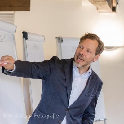 HEIJBLOM FOTOGRAFIE-evenementenfotografie-Fit-for-Work-Amersfoort-Ben-Tiggelaar-wijst-tekst-aan-op-een-flip-over