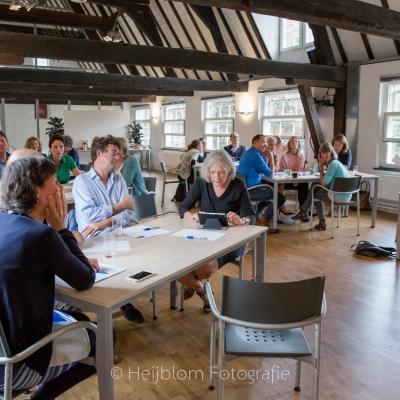 HEIJBLOM FOTOGRAFIE-evenementenfotografie-Fit-for-Work-Amersfoort-zaal-met-mensen-aan-tafels-luisteren-naar-Ben-Tiggelaar