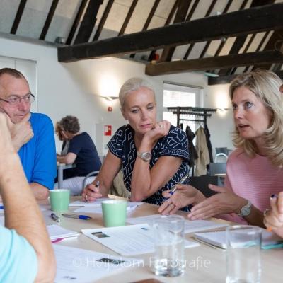 HEIJBLOM FOTOGRAFIE-evenementenfotografie-Fit-for-Work-Amersfoort-groepje-mensen-met-elkaar-in-gesprek-aan-tafel