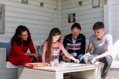 HEIJBLOM FOTOGRAFIE-familiefotografie-gezin speelt monopoly tijdens coronacrisis in de tuin