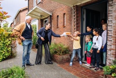 HEIJBLOM FOTOGRAFIE-Voordeurportret-oma geeft zelfgebakken cake aan de kinderen