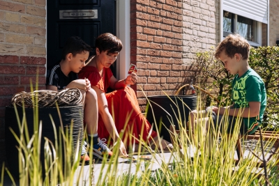HEIJBLOM FOTOGRAFIE-moeder en kinderen spelen een spelletje uno in de deuropening en voortuin