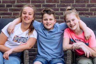 HEIJBLOM FOTOGRAFIE-Kinderfotografie-jongen met twee zussen voor een muur