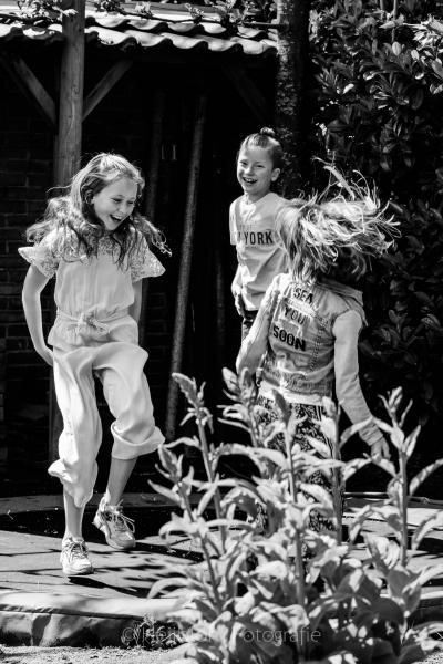 HEIJBLOM FOTOGRAFIE-kinderfotografie-zwart wit foto kinderen springen blij op de trampoline