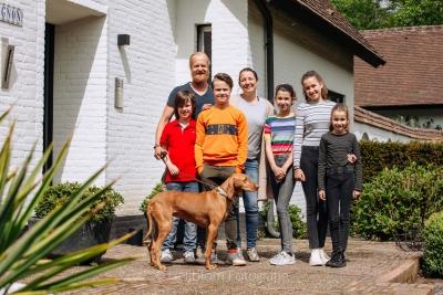 HEIJBLOM FOTOGRAFIE-Familiefotografie-gezin voor een huis met een bruine hond