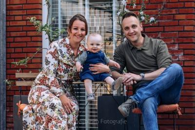 HEIJBLOM FOTOGRAFIE-thuisportretten in coronatijd-fotoshoot in de hoeksche waard-ouders met een baby met tuinpak in de tuin voor een bloesem boompje