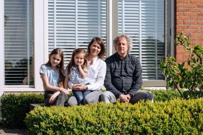HEIJBLOM FOTOGRAFIE-thuisportretten in coronatijd-gezinsfotografie hoeksche waard-gezin lekker in de zon op een bankje voor het huis