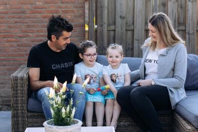 HEIJBLOM FOTOGRAFIE-gezinsfotografie ouders met kinderen op de bank in de tuin