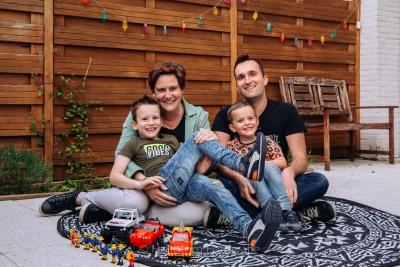 HEIJBLOM FOTOGRAFIE-gezin in de achtertuin op een rond kleed met brandweerman sam speelgoed