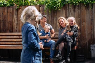 HEIJBLOM FOTOGRAFIE-gezinsfotografie foto met gezinnetje in de achtertuin op de houten tuinbank