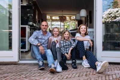 HEIJBLOM FOTOGRAFIE-vader met dochters zittend bij de openslaande deuren van een jaren 30 huis naar de achtertuin