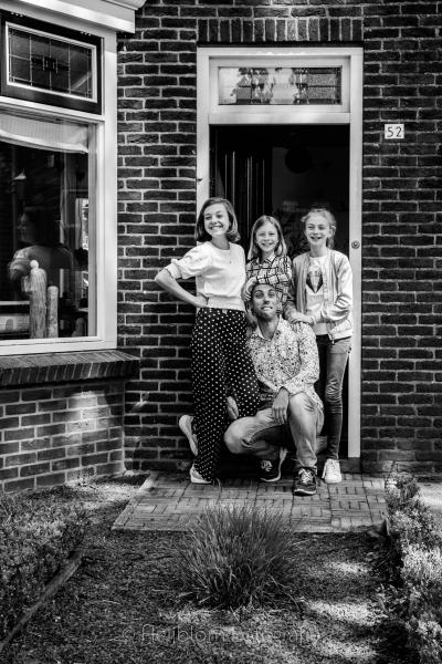 HEIJBLOM FOTOGRAFIE-zwart wit foto met vader en dochters in de deuropening