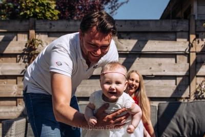 HEIJBLOM FOTOGRAFIE-vader slingert dochtertje in de lucht terwijl moeder lachend toekijkt vanaf de bank