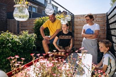 HEIJBLOM FOTOGRAFIE-familie sjoelt in de tuin tijdens thuisblijven in de coronacrisis