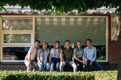 Heijblom Fotografie - Familie zit in de vensterbank voor hun huis onder de markies