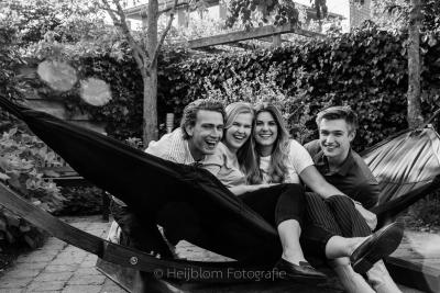 Zwart wit foto van broers en zussen zittend in een hangmat in de achtertuin tijdens de coronacrisis