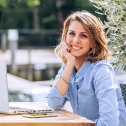 Vrouwelijke ondernemer achter laptop portret voor website